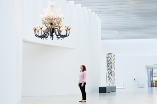 Woman looks up at a large glass chandelier in a white gallery