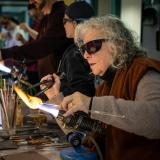 An elderly woman uses a flame to melt a clear rod of glass and shape it with a jack
