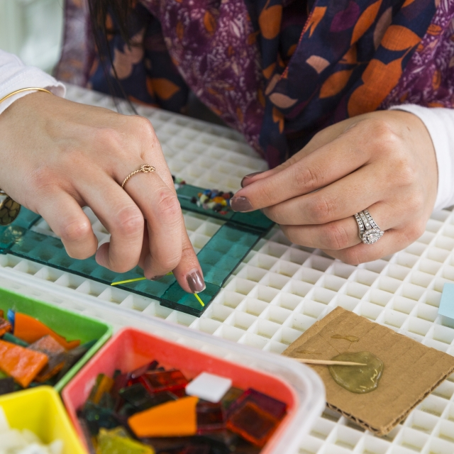 An adult adds pieces of multicolored cut glass to a transparent green frame