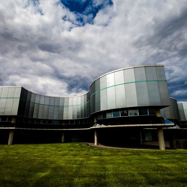 The outside of Birkerts Building is shown from a low angle and the sky above is filled with clouds