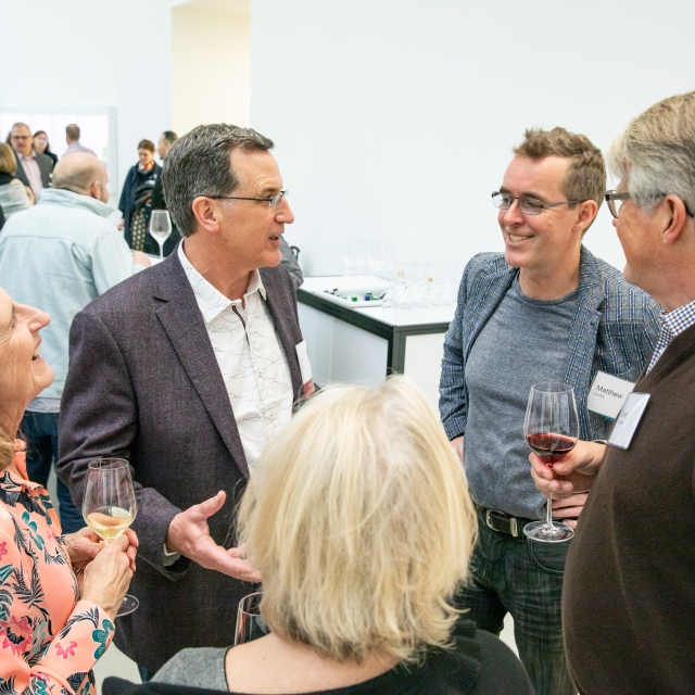 A group of members enjoy conversation and wine at the opening of 2019's New Glass Now exhibition